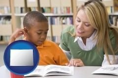 co a teacher helping a student with reading skills
