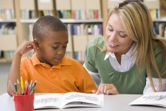 a teacher helping a student with reading skills